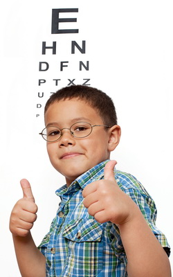 Eye Exam Chart in Scranton PA behind Happy Boy Wearing Glasses
